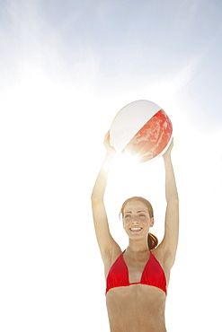 Young woman holding beach ball above head