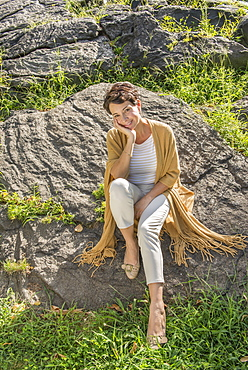 Mature woman sitting on rock