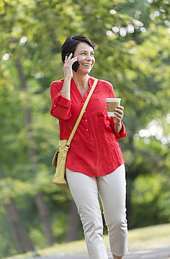 Mature woman talking on cell phone in park
