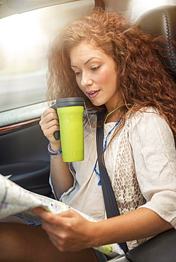 Woman sitting in car with map and disposable cup