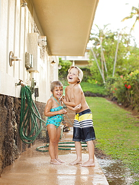 Children (2-3, 6-7) refreshing at outdoor shower, Kauai, Hawaii
