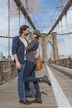 Happy couple embracing on Brooklyn Bridge, Brooklyn, New York