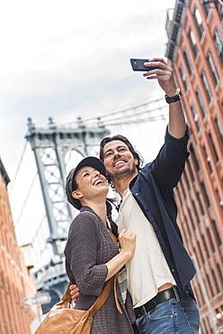 Couple taking selfie on street, Brooklyn Bridge in background, Brooklyn, New York