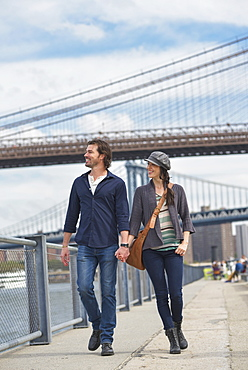 Couple walking on promenade, Brooklyn Bridge in background, Brooklyn, New York