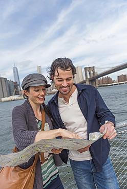 Happy couple reading map, Brooklyn, New York