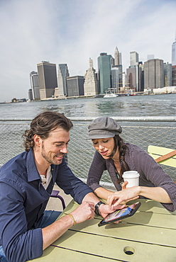 Happy couple sitting and using tablet pc with cityscape in background, Brooklyn, New York