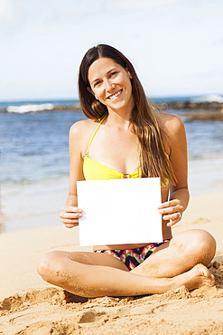 Portrait of young woman with blank paper sitting on beach, Kauai, Hawaii