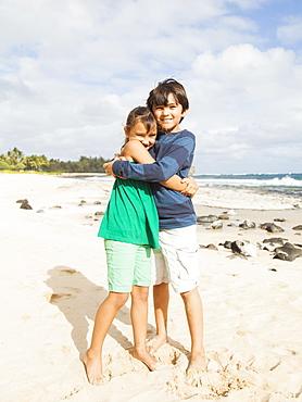 Portrait of girl (6-7) and boy (10-11) embracing on beach, Kauai, Hawaii