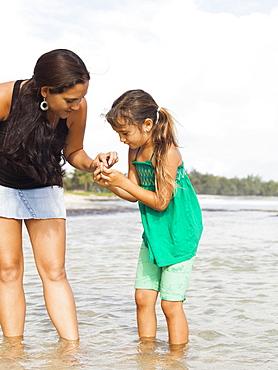 Girl (6-7) with mother walking in sea, Kauai, Hawaii