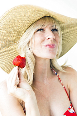 Studio portrait of blonde woman with sun hat holding strawberry