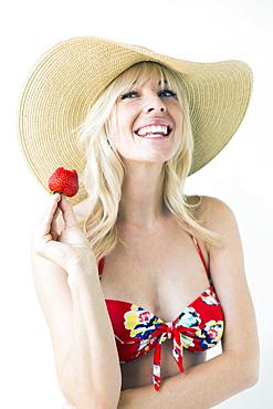 Smiling woman in bikini holding strawberry, studio shot