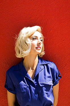 Close-up of Woman in blue dress posing against red wall in sunlight