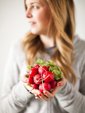 Portrait of attractive young woman holding radish