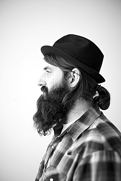 Profile of male character wearing long beard, hat and lumberjack shirt