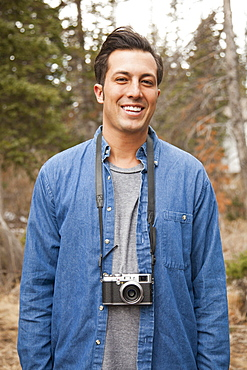 Portrait of young man with old fashioned camera in non-urban scene, Salt Lake City, Utah