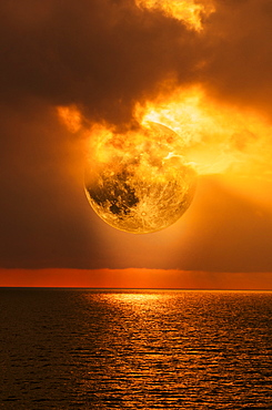 Moon and clouds at sunset over sea