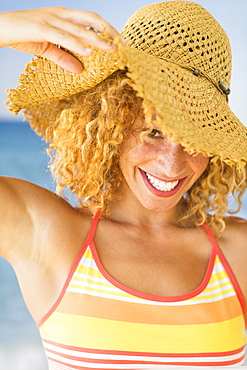 Portrait of smiling young woman in sun hat