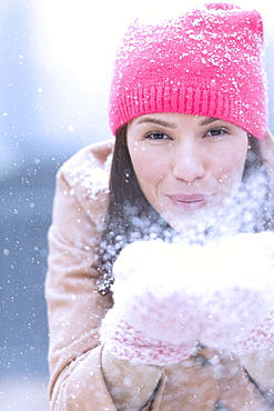 Portrait of woman blowing snow from hands