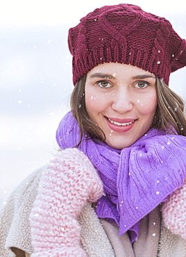Portrait of young woman wearing knit hat, gloves and scarf
