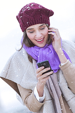 Young woman in wearing warm clothes and using mobile phone