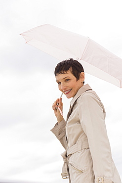 Portrait of smiling woman wearing raincoat and holding umbrella