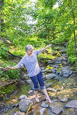 Senior woman crossing stream, Central Park, New York City