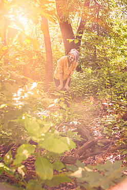 Senior woman hiking in sunny forest, Central Park, New York City