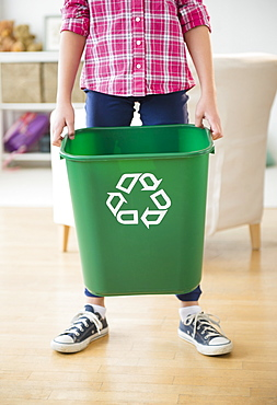 Close up of girl (8-9) holding recycle bin