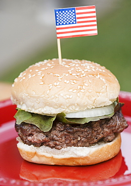 Still life of hamburger with small US flag