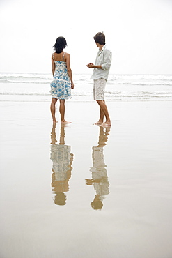 Couple standing on beach looking at waves