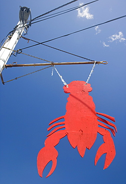 Lobster shaped sign under blue sky, Maine, United States