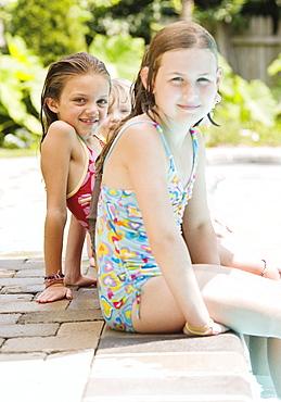 Girls sitting on edge of swimming pool