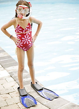 Girl in snorkeling gear standing at edge of swimming pool