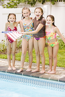 Girls waving American flag poolside