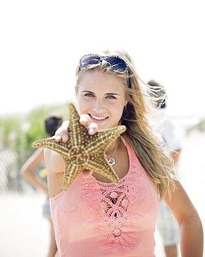 Woman holding up starfish