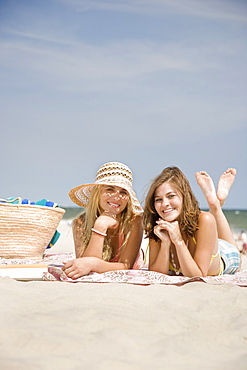 Friends laying on beach blanket