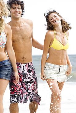 Friends walking in ocean surf