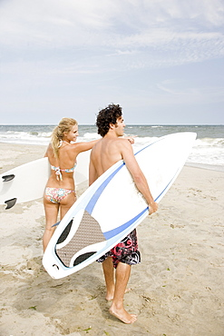 Couple holding surfboards at beach