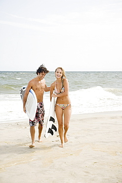 Couple carrying surfboards at beach