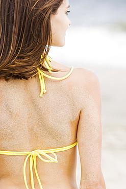 Woman in bikini with sand on back