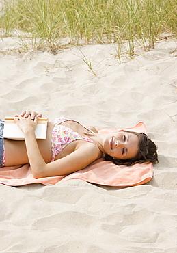 Woman laying on beach towel