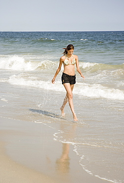 Young woman walking in ocean surf