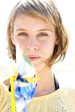 Woman blowing on pinwheel