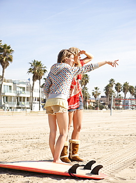 Two young women standing on beach