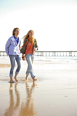 Two women walking on beach