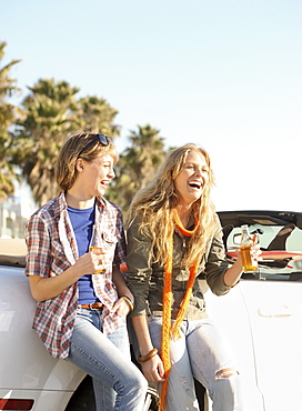 Two women drinking beer next to convertible