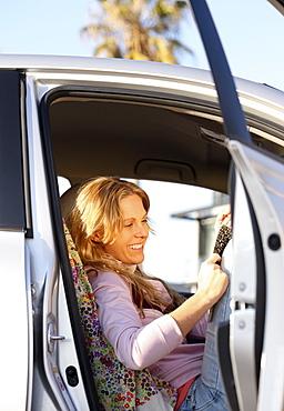 Woman sitting in car with door open
