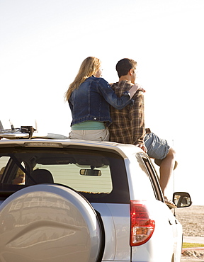 Couple sitting on top of car