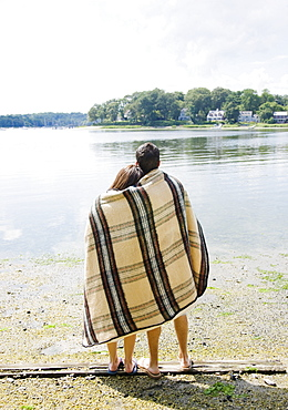 Couple wrapped in blanket looking out at lake
