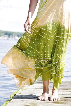 Wind blowing dress of woman standing on dock